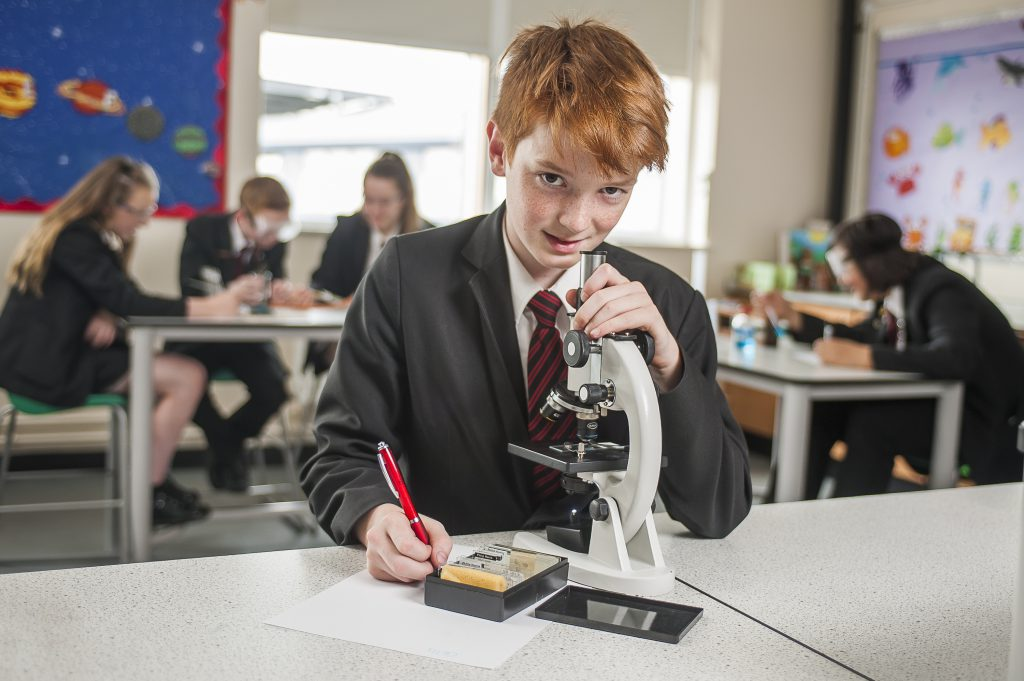 Student using a microscope in our science laboratory